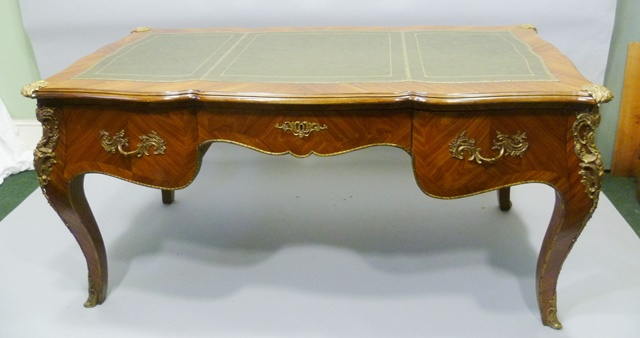 A 20TH CENTURY LOUIS XVI STYLE BUREAU PLAT having green leather tooled inset top, kingwood veneered surround, applied gilt metal mounts on three drawer front, raised on four cabriole legs with sabots, 81cm x 1.7m