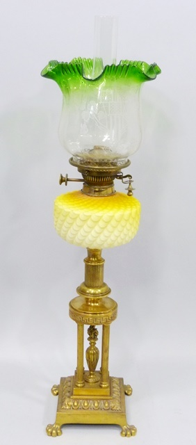 A VICTORIAN BRASS OIL LAMP having green and clear etched shade, a Hinks double sided flat wick burner, yellow pineapple glass reservoir upon a four pillar gazebo style stand with cast square base and lobed feet, 80cm high