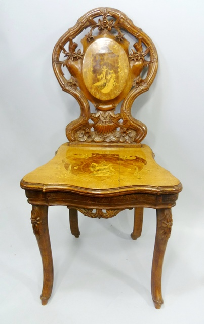 A MID 19TH CENTURY CONTINENTAL, PROBABLY SWISS, WALNUT AND MARQUETRY INLAID HALL CHAIR having ornately carved and inlaid back, serpentine seat with musical mechanism, raised on cabriole forelegs