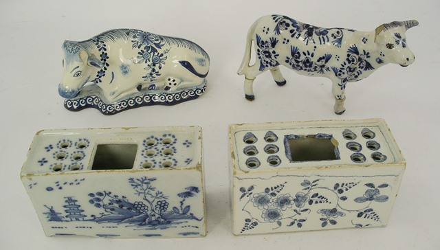TWO EARLY 19TH CENTURY DELFT TIN GLAZED EARTHENWARE FLOWER BRICKS, each having a pierced decorated top, painted surround with pseudo oriental decoration, 7cm x 12cm and 6cm x 12cm, and TWO LATER DELFT COWS, various