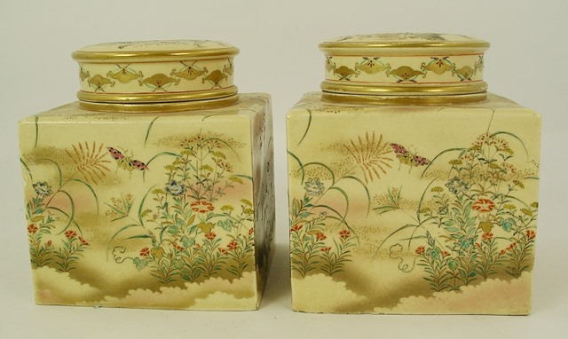 A PAIR OF EARLY 20TH CENTURY JAPANESE SATSUMA TEA CADDIES, each having a detachable lid with gilded ribbed decoration, upon a cube shaped body, painted with floral and fauna in polychrome enamels, 16cm high