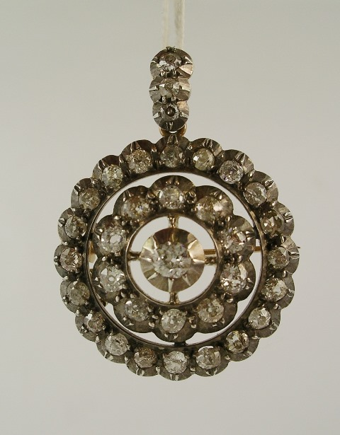 A VICTORIAN DIAMOND SILVER AND GOLD MOUNTED BROOCH PENDANT comprising old cushion cut brilliants in silver top with gold back, 20 stones outer row, 10 stones inner row and centre, with three stones in the hook, approximately 3cm diameter