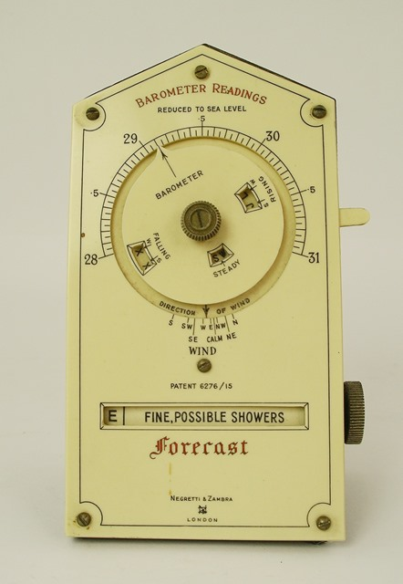 AN EARLY 20TH CENTURY NEGRETTI & ZAMBRA FORECASTER, having an ivorine front calibrated with barometer readings, dials and levers, displaying various types of weather, patent no. 6276/15, 15cm high, and ANOTHER EARLY 20TH CENTURY DESK TOP BAROMETER/HYGROMETER, having chromed fittings and a black aluminium finished base, unnamed, 13cm x 25cm