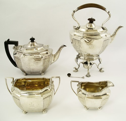 J.G. & W.L. FOR GOLDSMITHS AND SILVERSMITHS CO. A FOUR PIECE SILVER TEA SET, each of octagonal elongated form, having guilloche wire rim and reeded side panels, on ball feet, comprising kettle on stand, teapot, sugar and milk, London, 1892, kettle 986g, teapot 576g, sugar 277g, milk 169g,  total weight 2008g