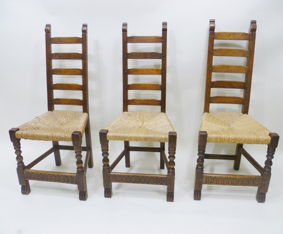 PURPORTEDLY BY RUPERT GRIFFITHS A SET OF SIX 1920s JACOBEAN STYLE DINING CHAIRS, each having a five rung back, strung seat, raised on turned forelegs united by a carved and moulded rance