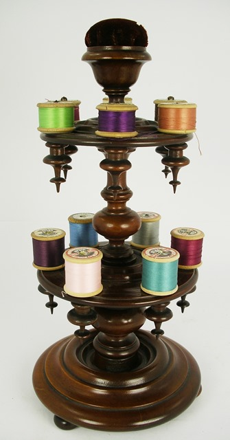 A VICTORIAN TREEN TURNED WOOD SEAMSTRESSS COTTONS DISPENSER having pink cushion top, knopped uprights, two tiers, each with six cottons and pendants, on a circular base, 38cm high