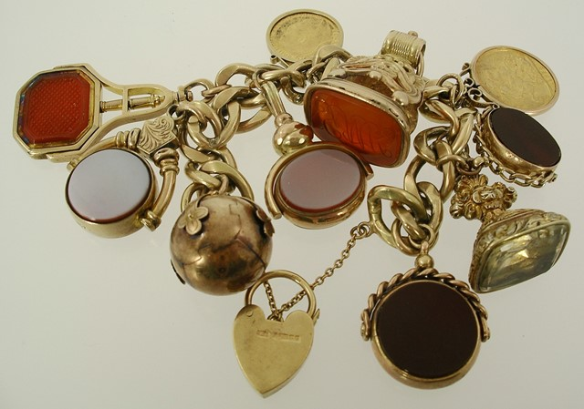 A 9CT GOLD HEAVY HAMMERED CURB LINK PADLOCK BRACELET, having six various gold and gilt metal hardstone seals, three bloodstone and three cornelian, a Masonic ball cross charm, a Queen Victoria 1889 Jubilee gold full sovereign and an Edward VII 1902 half sovereign, each in gold coloured metal, later wrap scroll mounts all attached, gross weight 159g.