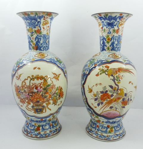 A PAIR OF 20TH CENTURY ORIENTAL PORCELAIN VASES decorated with flowers, birds and foliage in the Imari palette, 47cm high