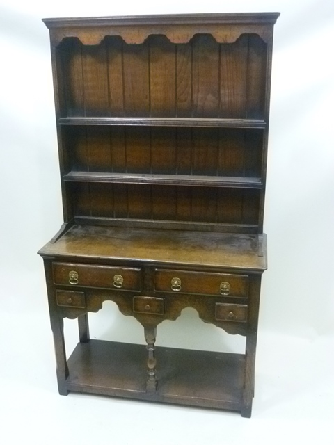 A 20TH CENTURY GEORGIAN STYLE OAK DRESSER having shelved superstructure on a base with plank top over five drawers, raised on three turned and squared chamfered front supports with pot shelf stretcher, 170cm x 92cm