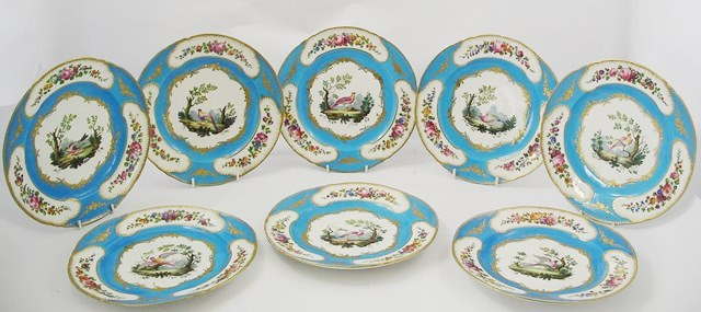 A SUITE OF EIGHT SEVRES PORCELAIN PLATES, each hand painted with exotic birds in landscape, turquoise borders with floral vignettes, 24cm diameter