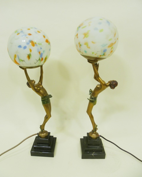 A PAIR OF PAINTED PROBABLY SPELTER FIGURAL TABLE LAMPS of semi-naked Art Deco ladies in athletic poses, having mottled marble spherical glass shades and stepped black marble plinth, 56cm high tallest