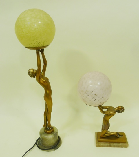TWO VARIOUS PAINTED PROBABLY SPELTER FIGURAL TABLE LAMPS, of one naked and one semi-clad female in semi-athletic poses with pink mottled spherical shade, one kneeling on a rectangular plinth base, 38cm high, one reaching high on tip-toe on stepped onyx base with spherical shade, 63cm high
