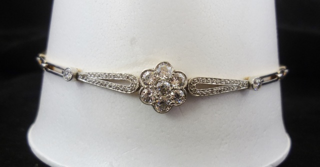 A 20TH CENTURY VICTORIAN STYLE DIAMOND BRACELET having a central floret of 7 millegrain, set brilliants, flanked by two loops of diamond chips on a stretch link bracelet, all of white gold coloured metal upper and yellow gold coloured metal construction, unmarked