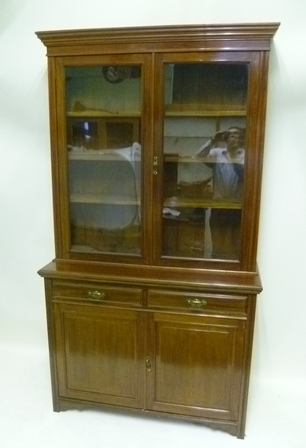 A LATE VICTORIAN/EDWARDIAN MAHOGANY CABINET BOOKCASE, the upper section with moulded pediment over twin glazed doors, enclosing four shelves, the base with twin in-line drawers over fielded panel doors, raised on bracket style feet, 2.23m x 1.22m
