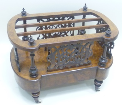 A VICTORIAN WALNUT CANTERBURY having fancy lobed top with four finials fitted uprights, on a base with drawer, raised on four short turned legs with brass cup castor terminals.