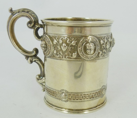 JOHN RUSSELL A VICTORIAN SILVER CYLINDRICAL MUG  having ornate banded mask and floral banded decoration and scroll handle, period crested and gilt interior, Glasgow 1869, 9cm high, 154g