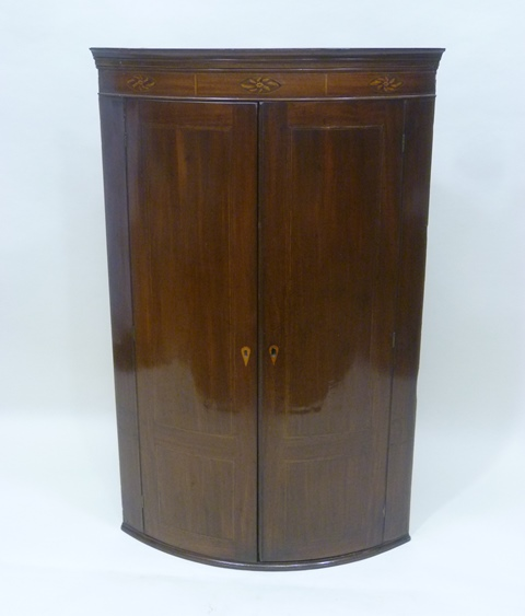 A LATE GEORGIAN MAHOGANY BOW FRONTED HANGING CORNER CUPBOARD having moulded pediment, triple floral stylised inlaid frieze, 1.2m high x 76cm wide
