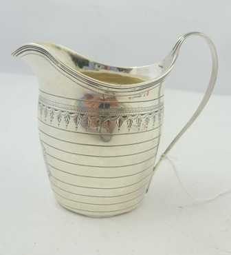 MARKS RUBBED A GEORGE III SILVER OVAL MILK JUG, having wavy reeded rim and drawn handle, the body wriggle work banded and tooled with bright cut pendants, London 1795, 102g