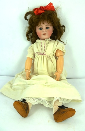 A BISQUE HEADED DOLL having auburn wig, closing blue eyes, open mouth, on a composition body, wearing a cream pinafore dress with lace under garments and leather shoes, 50cm tall