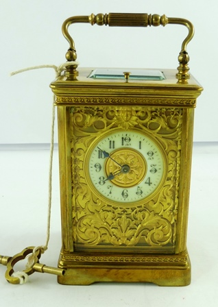 A LATE 19TH/EARLY 20TH CENTURY FRENCH REPEATER CARRIAGE CLOCK having moulded style case with guilloche decoration, eight day mechanism with original platform escapment faced by an ornate gilt mask with Arabic enamel chapter and key, 19cm high