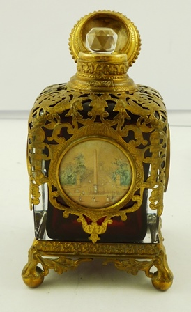A 19TH CENTURY PROBABLY FRENCH RUBY AND CLEAR OVERLAID LEAD CRYSTAL PERFUME BOTTLE, mounted with fretted brass and having four vignettes of well known classic buildings, 12cm high