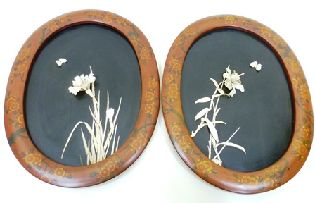 A PAIR OF EARLY 20TH CENTURY JAPANESE LACQUERED  PANELS with carved bone applied floral decoration, 44cm x 31.5cm oval in floral lacquer painted wood effect frames