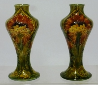 WILLIAM MOORCROFT A PAIR OF LATE 19TH CENTURY MACINTYRE FLORIAN EARTHENWARE BALUSTER VASES, having tube lined floral decoration over mottled green glaze, each vase signed, 16cm high