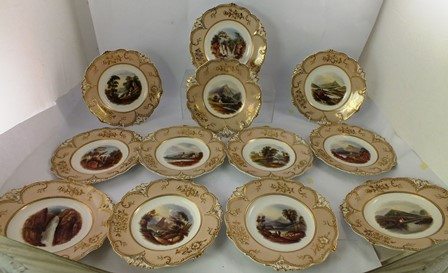 A VICTORIAN STAFFORDSHIRE PORCELAIN DESSERT SET, comprising 11 x 25cm diameter plates and 1 x elevated dish, each having hand painted landscape centre, bordered by creamy orange and gilded cast foliated rims, and titled Bonniton Lynn Loch Cullin, Loch Mabon and Castle etc.