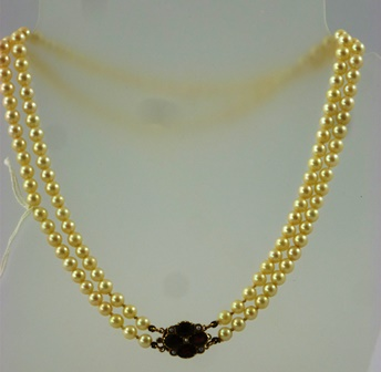 A TWO ROW SLIGHTLY GRADUATED CULTURED PEARL NECKLET, having seed pearl and four stone garnet clasp