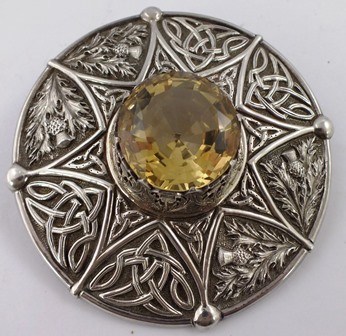 R.W. FORSYTH LIMITED, GLASGOW & EDINBURGH AN EDWARDIAN SUBSTANTIAL SILVER AND CITRINE/CAIRNGORM SET KILT BROOCH, having multi faceted central stone and bordered by thistle and Celtic decoration, Edinburgh 1909, gross weight 110g.