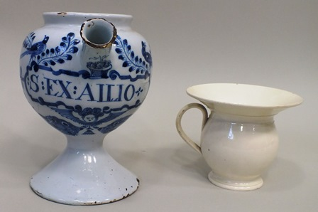 A 17TH CENTURY PROBABLY LONDON DELFT WET DRUG JAR decoratively painted with birds and a winged face mask, bearing the legend :S:EX:AILIO believed sulphur extract of garlic, 19cm high, together with a LATE 18TH/EARLY 19TH CENTURY CREAMWARE SPITTOON10cm high (2 items)