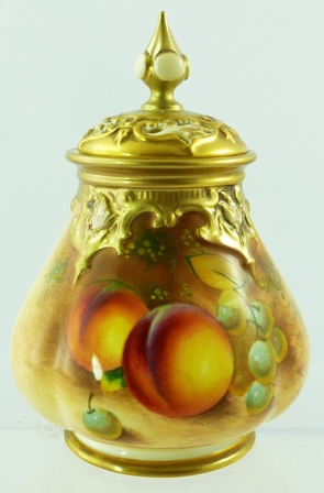 FRANK ROBERTS A ROYAL WORCESTER PORCELAIN VASE/POT POURRI having cast fretted lid with finial and pear shaped body painted with peaches and grapes and highlighted with gilt, shape H291, revised mark no.4360 Godden c.1960, 17cm high
