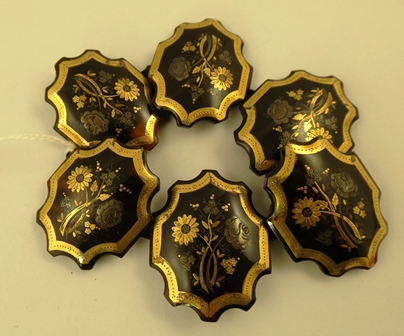 A VICTORIAN JET AND TORTOISESHELL MOUNTED GOLD AND SILVER SIX PLAQUE FLEXIBLE BRACELET, each plaque displaying flowers in a gold applied surround
