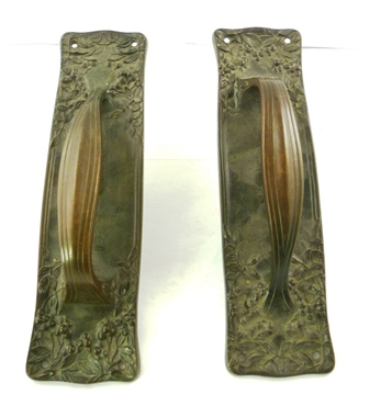 A PAIR OF ART NOUVEAU CAST AND PATINATED DOOR HANDLES of generous size, each moulded with fruit and foliage, 39cm long