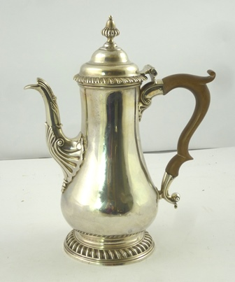 BENJAMIN GODFREY A GEORGE III SILVER COFFEE POT having hinged lid with lobed knop, plain baluster body with banded gadroon rim and foot and later fibre handle, London 1762, 732g, 26cm high