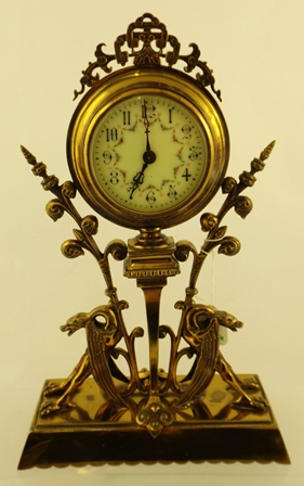 A LATE 19TH/EARLY 20TH CENTURY GILT BRASS MANTEL TIMEPIECE having ornate case with fanned foliate scrolls, raised on twin mythical beasts, eight day French mechanism with period platform cylinder escapement faced by an Arabic enamelled floral garland decorated dial, 35cm high x 22cm wide