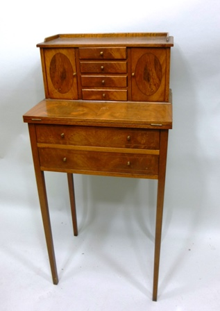 A 1960s/1970s MAHOGANY VENEERED SHERATON STYLE LADYS WRITING TABLE having superstructure with four drawers and twin flank cupboards, fold out top over twin drawers, raised on square tapered legs, 1.02m high x 48cm wide