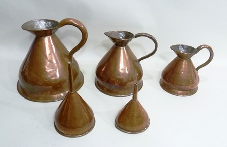 A GRADUATED SET OF THREE 19TH CENTURY COPPER HAYSTACK MEASURES, for measuring malt whisky, two gallons, 1 gallon and half gallon, flared skirt bases with castellated seams, impressed standard stamp marks inside rim (Vendors provenance that they wereused at Ruddles Brewery pre-war)