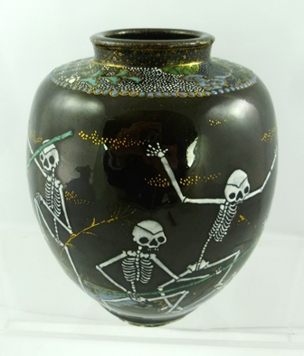 A JAPANESE VASE the black ground painted with skeletons fighting with green bamboo poles, partly gilded and decoratively painted in blue and turquoise enamels, 19cm high