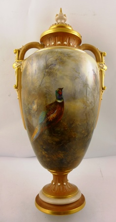 JAMES STINTON AN EDWARDIAN ROYAL WORCESTER PORCELAIN MONUMENTAL VASE, having detachable lid with fancy finial and Greek key gilt rim, ovoid body with pheasants in habitat, on a fluted and beaded turned pedestal foot, dated indistinctly possibly 1905, 63cm high