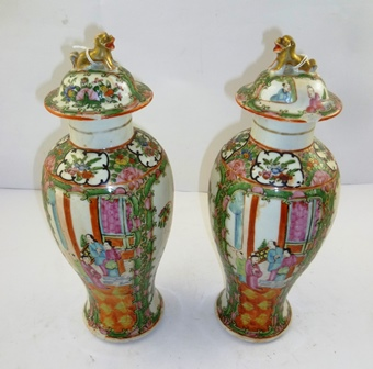 A PAIR OF EARLY 20TH CENTURY CHINESE CANTON EXPORT PORCELAIN VASES AND COVERS, each with detachable lids with Kylin finials and allover decorated in polychrome palette, base with four character blue mark, 33cm high