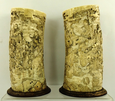 A PAIR OF JAPANESE MEIJI PERIOD CARVED IVORY TUSK VASES, carved in the round with processions of courtly figures, musicians and wise men, raised on gilded hardwood bases, overall 25.5cm high